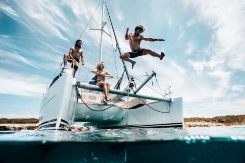 Ragazzi si tuffano dal catamarano durante escursione nell'Arcipelago di La Maddalena